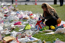© Licensed to London News Pictures. 09/04/2017. London, UK.  Members of the public observe flowers left outside Carriage gate at The Houses of Parliament on the day that the coffin of PC Keith Palmer arrived at Chapel of St Mary Undercroft within the Palace of Westminster, ahead of his funeral tomorrow (Mon). PC Palmer was killed in a terror attack when Khalid Masood drove a car at pedestrians over Westminster Bridge and then attempted to enter Parliament with a knife. Photo credit: Tolga Akmen/LNP