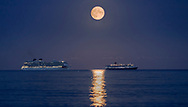 The Harvest Moon rises above P&O Cruises' largest ship, Britannia (left) and Cunard's Queen Victoria as they sit at anchor in Weymouth Bay. The cruise industry has suffered a complete shutdown during the covid-19 pandemic and many vessels are currently waiting at various anchorages around the coast of Great Britain and the world.<br /> Picture date Tuesday 1st September, 2020.<br /> Picture by Christopher Ison. Contact +447544 044177 chris@christopherison.com