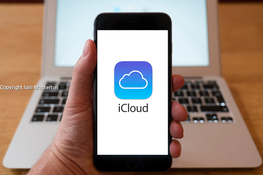 Using iPhone smartphone to display logo of Apple iCloud , cloud based storage and backup service
