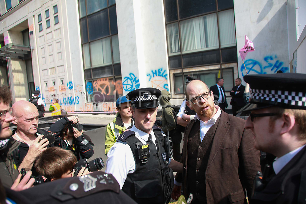 Three activists super glued themselves to the glass doors of the Shell Building and two scaled the glass awning in protest against the oil companys continued exploitation of fossil fuels, 15th April 2019, Central London, United Kingdom. Simon Bramwell is arrested. A number of arrests were made. The environmental protest group Extinction Rebellion has called for civil disobedience and peaceful protest to force the British government to take drastic action on climate change. The group wants the governenmet to tell the truth and admit that the impact of climate change is much more severe than they say and that action to mitigate catastrophic climate change is urgent.