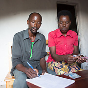 CAPTION: Stanislas is happy that he and his wife have come this far, and that his children are receiving quality secondary education at boarding school. The fees are expensive, however, and the couple admit to being a little concerned about generating sufficient cash to ensure they'll continue to afford the fees over the terms to come. While Stanislas has seen an overall increase in personal income, the profits he makes now are largely channeled towards school fees. This means that he and his wife have not seen a significant rise in their disposable income and have to budget carefully, something they readily accept because they strongly believe that investing in their children's education is a vital step towards ensuring their quality of life. They know that helping their children to complete their secondary schooling is a huge responsibility, but they say they're hopeful that hard work and God's guidance and support will help them succeed in this. LOCATION: Rushikiri Village, Kimuna Cell, Rusatira Sector, Huye District, South Province, Rwanda. INDIVIDUAL(S) PHOTOGRAPHED: Stanislas Iriboneye (left) and Clementine Nibagwire (right).