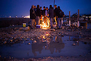 Plestinian man huddle near a bon fire as they wait for their employer, after crossing into Israel near the city of Kfar Saba.<br /> Each day Palestinian workers pass through cross points like this one in order to work in Israel.