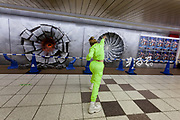 A Japanese woman in costume throws a pretend punch at three craters in a wall advertising the Jump Force video game for Play Station, X-box and Window PC in Shinjuku Station, Tokyo, Japan. Friday February 22nd 2019. Jump Force  game brings together all the most popular characters from the Shonan Jump manga comics.and was released on February 15th. The punch wall represents the effect of a power punch from characters Son Goku of Dragonball, Naruto and Luffy from One Piece and runs to February 24th