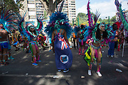 Parade dancers in feather costumes stop in the street at the base of Trellick Tower on Monday 28th August 2016 at the 50th Notting Hill Carnival in West London. A celebration of West Indian / Caribbean culture and Europes largest street party, festival and parade. Revellers come in their hundreds of thousands to have fun, dance, drink and let go in the brilliant atmosphere. It is led by members of the West Indian / Caribbean community, particularly the Trinidadian and Tobagonian British population, many of whom have lived in the area since the 1950s. The carnival has attracted up to 2 million people in the past and centres around a parade of floats, dancers and sound systems.