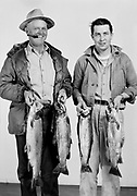 "9336-LR02""Charles Kuhl. Rainbow Trout caught in Blitzen River. May 1, 1948"" studio portrait of two men holding fish, one is smoking a cigar."