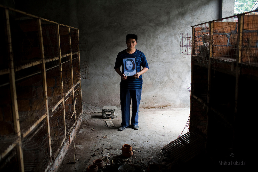"""Losing a child has been described as the worst kind of loss anyone could possibly go through. In the May 12, 2008 earthquake that struck China's Sichuan Province, nearly 70,000 people were killed, with many thousands more missing and likely dead. Among them, at least 9,000 of them were schoolchildren  who were crushed to death by falling school buildings. <br /> Why did so many schools collapse? Victims of family, most of them are farmers and migrant workers, suspect corruption was behind these poorly built schools, known  as """"tofu construction."""" The government promised further investigation initially but later most of the parents were forced to sign the agreement that they will accept money and will not further hold govenment accountable for further investigation.<br /> Yu Ming Fa, 36, holding a picture of his daughter Yu Huan, 10, is seen at a rabbit house at Fuxin No.2 Primary  School in Wufu, Sichuan province. Yu is angry about a rabbit house. """"School can feed rabbits to make money. It pays more attention to rabbit business  than safety of children."""""""
