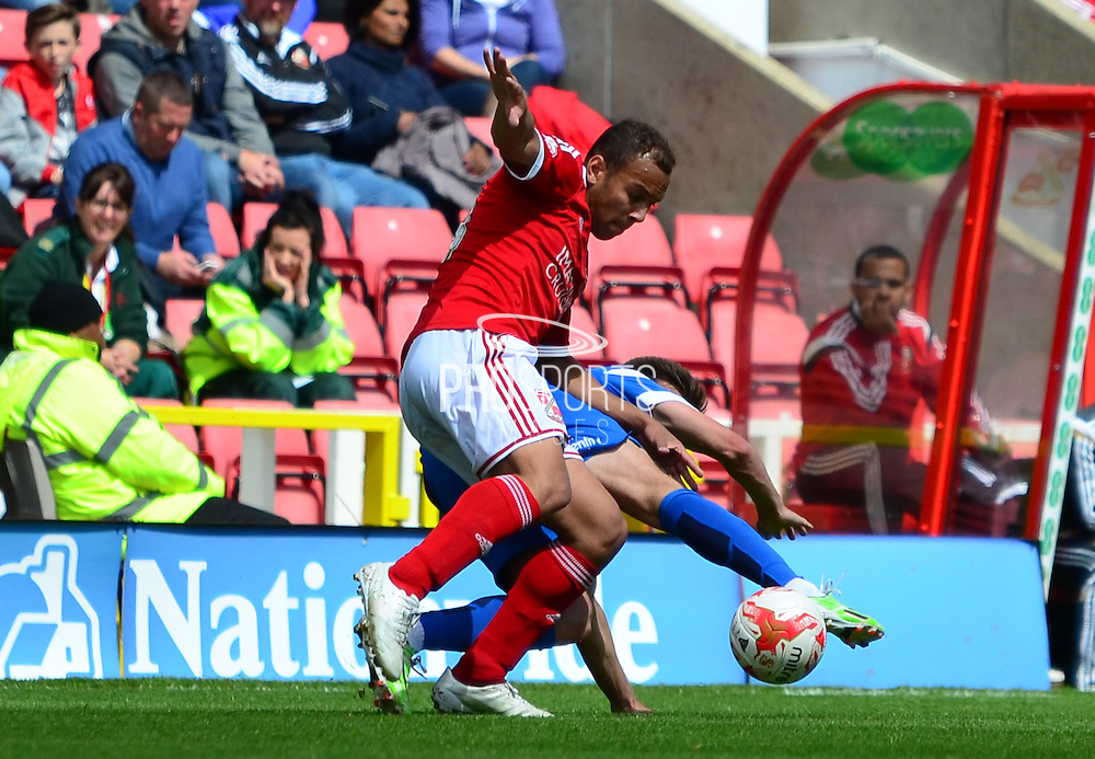 Joshua Cook being tackled during the Sky Bet League 1 match between Swindon Town and Leyton Orient at the County Ground, Swindon, England on 3 May 2015. Photo by Alan Franklin.