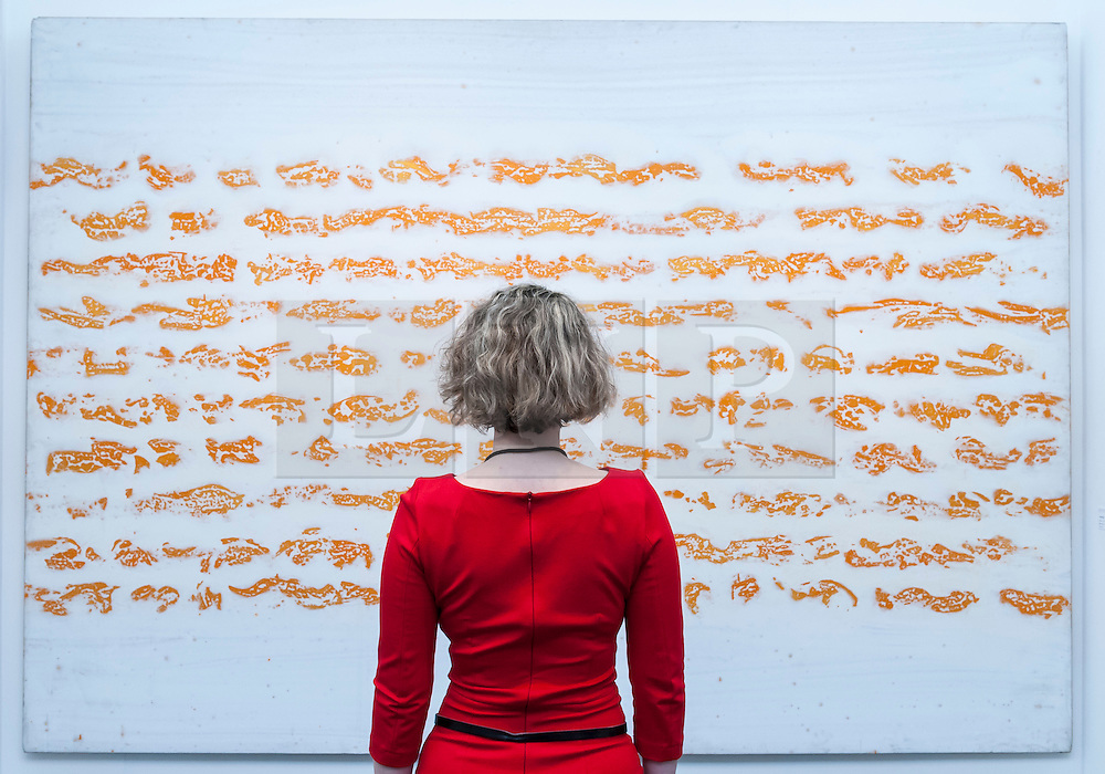 """© Licensed to London News Pictures. 19/05/2016. London, UK. A visitor looks at Judit Reigl's """"Progress"""".  Art16 opens at Olympia, in west London.  Now in its fourth edition, the fair brings together over 100 galleries from more than 30 countries showcasing a diverse cross-section of work by contemporary artists from around the world for buyers and art enthusiasts to visit. Photo credit : Stephen Chung/LNP"""