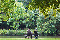A couple enjoy the tranquility of a shady spot by the River Thames at Sunbury, July 03 2019.