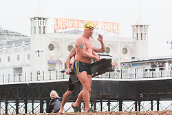 © Licensed to London News Pictures. 06/12/2015. Brighton, UK. Members of the Brighton and Hove Sea Swimming Club brave the powerful waves that hit Brighton seafront as the South Coast gets some of the fallout of storm Desmond. Today December 6th 2015. Photo credit: Hugo Michiels/LNP