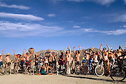 """Critical Tits"" bicycle parade participants yelling, ""Breasts are Beautiful"" at Burning Man. Burning Man is a performance art festival known for art, drugs and sex. It takes place annually in the Black Rock Desert near Gerlach, Nevada, USA."