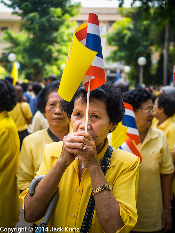 28 NOVEMBER 2014 - BANGKOK, THAILAND:  A woman with the Thai and Monarchal flags prays for Bhumibol Adulyadej, the King of Thailand, at Siriraj Hospital. The King was born on December 5, 1927, in Cambridge, Massachusetts. The family was in the United States because his father, Prince Mahidol, was studying Public Health at Harvard University. He has reigned since 1946 and is the world's currently reigning longest serving monarch and the longest serving monarch in Thai history. Bhumibol, who is in poor health, is revered by the Thai people. His birthday is a national holiday and is also celebrated as Father's Day. He is currently hospitalized in Siriraj Hospital, recovering from a series of health setbacks. Thousands of people come to the hospital every day to sign get well cards for the King. People wear yellow at events associated with the King because he was born on a Monday, and yellow is Monday's color in Thai culture. It's also the color of the monarchy.      PHOTO BY JACK KURTZ