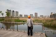 A construction worker stands on a platform overlooking a pond near residential buildings in the Jiading district of Shanghai, China, on Monday, April 11, 2016.