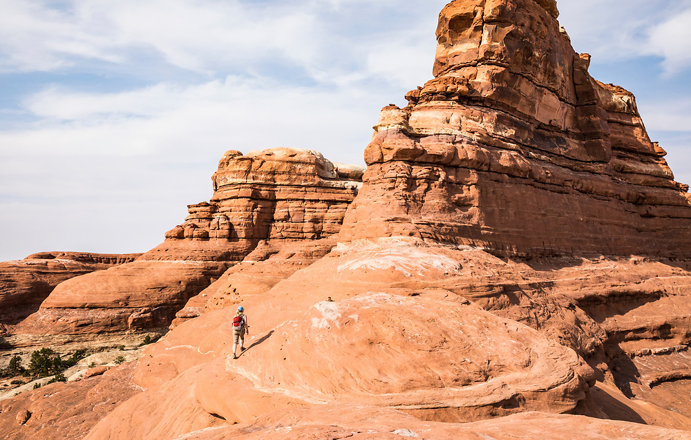 A woman hiking in the Needles District of Canyonlands National Park, Utah, USA.