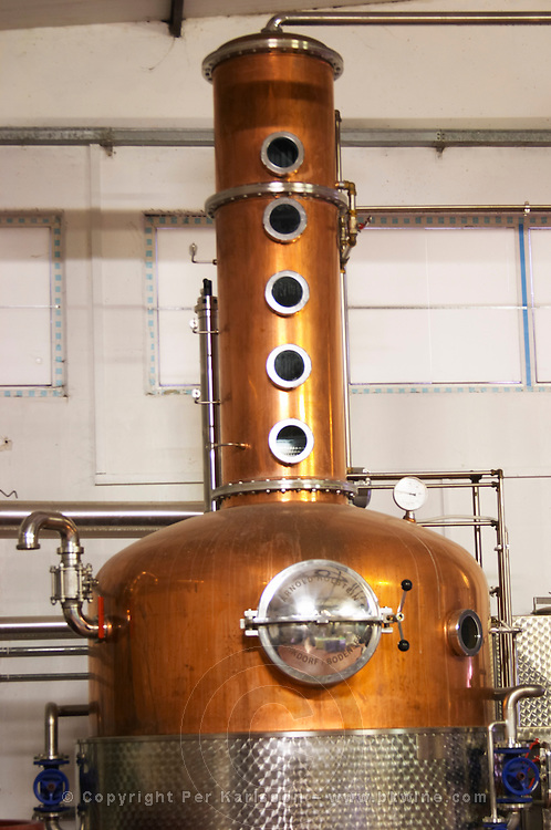 A distillation machine still in stainless steel and copper with narrow column. Hercegovina Produkt winery, Citluk, near Mostar. Federation Bosne i Hercegovine. Bosnia Herzegovina, Europe.