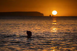 © Licensed to London News Pictures. 01/12/2020. Mudeford, UK. A swimmer, in the sea off Mudeford in Dorset, watches as the winter sun rises over The Needles on the Isle of Wight. Most of England is experiencing low temperatures and clear skies today on the first day of the Meteorological winter. Photo credit: Peter Macdiarmid/LNP