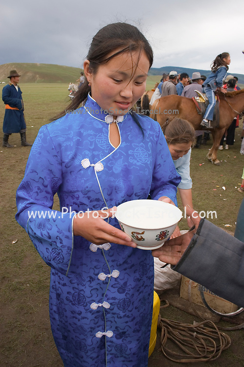 young girl serving a drink in a bowl at the traditional horse back races at Nadaam, Mongolia