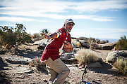 SHOT 10/16/16 9:58:17 AM - Paul Hobson of Steamboat Springs, Co. flashes the Heisman pose while playing catch during a White Rim mountain biking trip in Canyonlands National Park just outside of Moab, Utah. The White Rim Road is a 71.2-mile-long unpaved four-wheel drive road that traverses the top of the White Rim Sandstone formation below the Island in the Sky mesa of Canyonlands National Park in southern Utah in the United States. The road was constructed in the 1950s by the Atomic Energy Commission to provide access for individual prospectors intent on mining uranium deposits for use in nuclear weapons production during the Cold War. Four-wheel drive vehicles and mountain bikes are the most common modes of transport though horseback riding and hiking are also permitted.<br /> (Photo by Marc Piscotty / © 2016)