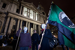 © Licensed to London News Pictures. 28/02/2012. LONDON, UK. Two protesters wearing Guy Fawkes masks and carrying an 'Anonymous' flag stand outside a cordon as police and bailiffs remove the Occupy London campsite in London today (28/02/21). After being camped outside St Paul's Cathedral in London for four months anti-capitalist Occupy London demonstrators were tonight evicted by police and bailiffs who moved in shortly after midnight. Photo credit: Matt Cetti-Roberts/LNP