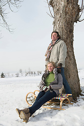 Couple relaxing on sledge, Bavaria, Germany