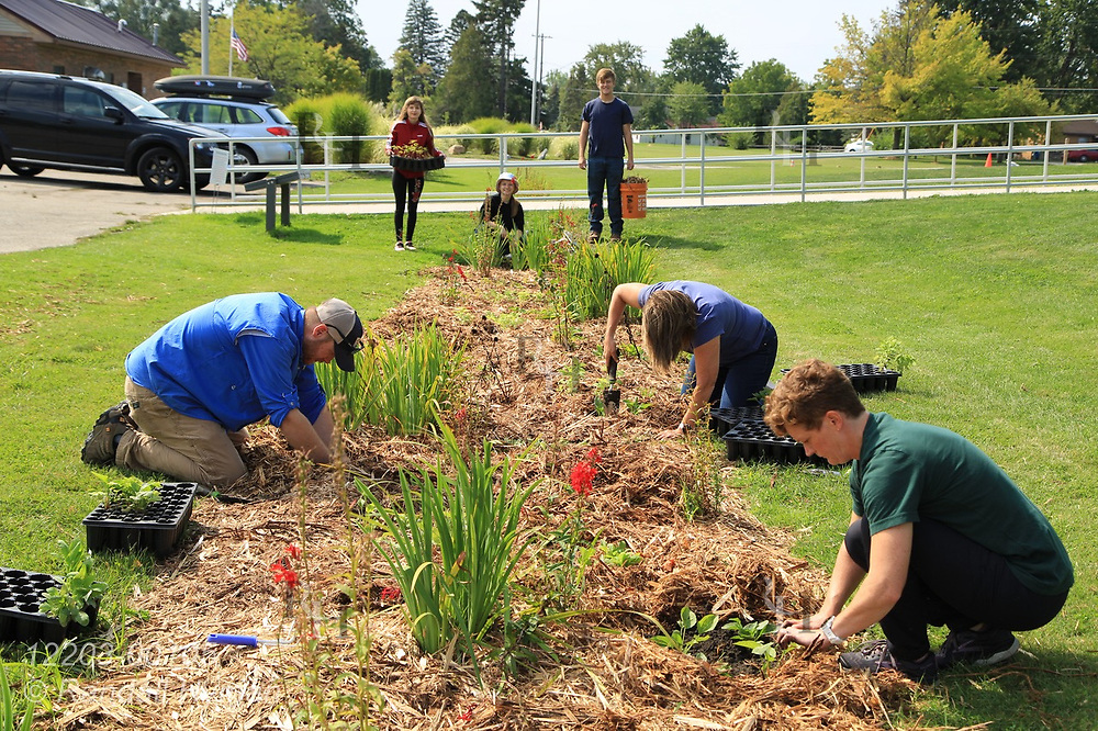 High school environmental sciences students, science teacher Luke Freeman, Bay Area Community Foundation CEO Diane Fong, and Huron Pines community program director Abby Ertel plant wildflowers in bioswale of rain garden at River Side Park in Au Gres, Michigan.
