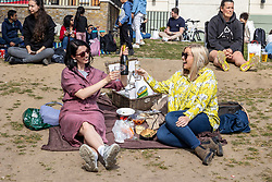 Licensed to London News Pictures. 18/04/2021. London, UK. Hannah Curran (left) and Emily Wilkes enjoy a picnic in the sunshine along the Thames at Richmond, South West London on the first weekend of the easing of Covid-19 restrictions. Shops, pubs, bars and restaurants are now serving customers for the first time in over 4 months as a mini heatwave is set to hit the UK this week with temperatures predicted to reach up to 18c in London and the South East. Photo credit: Alex Lentati/LNP