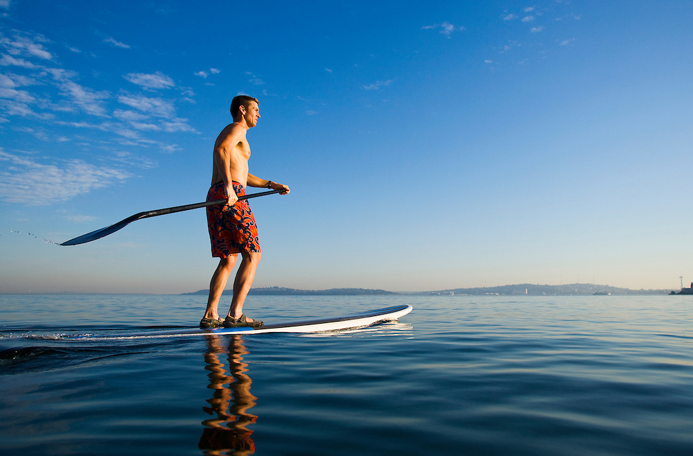 A man on a stand up paddle board on the Puget Sound near Seattle, WA.