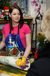 Florist wrapping up flowers for a customer in flower shop,