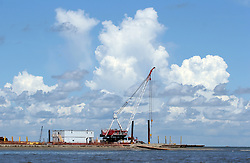 21 August 2010. East Grand Terre Island, south Louisiana. <br /> A crane and other heavy equipment continue efforts to fortify newly created sand berms where the Gulf of Mexico meets Barataria Bay. The controversial new 'islands' are part of a grander scheme to boost efforts to save the wetlands. To date the islands have done a good job taking on oil, preventing a great deal of it from entering the Bay beyond.<br /> Photo credit; Charlie Varley/varleypix.com