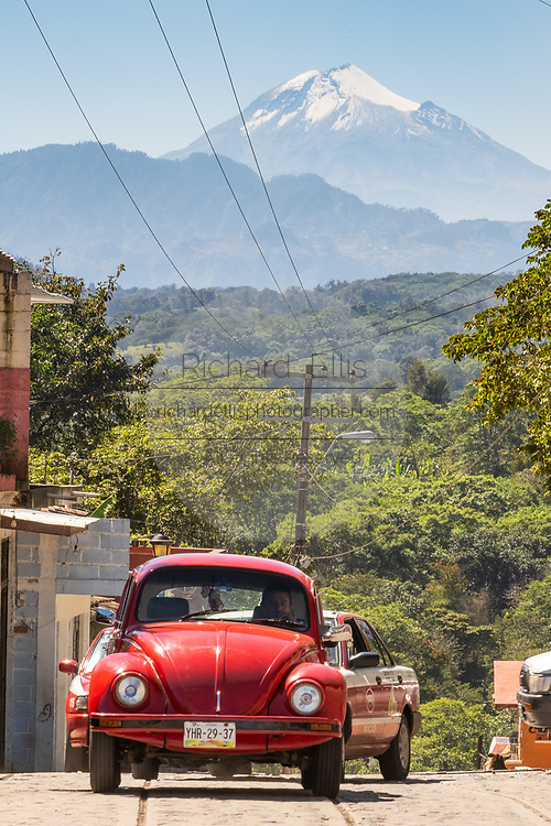 A red Volkswagen beetle drives up a hill with the snowcapped Cofre de Perote volcano behind near Xico, Veracruz, Mexico. The inactive volcano last erupted 900-year-ago and is the eighth highest mountain in Mexico.