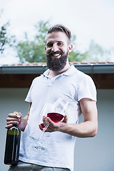 Portrait of a young man holding red wine with glasses, Bavaria, Germany