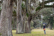 An woman walks along the ancient Live Oak trees covered in Spanish moss at the Fort Frederica National Monument, the original colonial settlement in St. Simons Island, Georgia. Fort Frederica was established by Georgia founder James Oglethorpe in 1736 to serve as a bulwark against the Spanish settlements in Florida,