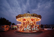 An empty fairground ride merry-go-round with lights on, 10th May 1980, Paris, France.