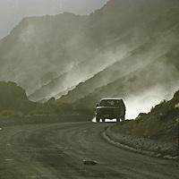 Car drives on dusty Chalk Bluff Road near Owens River.