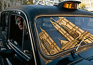 London Cab with reflection of Westminster Abbey in its window.