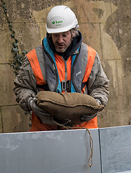 © Licensed to London News Pictures. 01/02/2021. Weybridge, UK. A worker holds a sand bag while installing flood defences along the river Thames at Weybridge in Surrey. Extra precautionis being taken because In 2014 Weybridge and the surrounding area was badly hit by flooding. Photo credit: Ben Cawthra/LNP