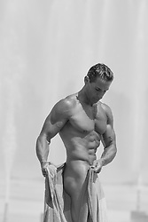 nude muscular man wrapping a towel on his waist