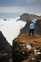 Person watches large winter waves crash against cliffs at Butt of Lewis, Isle of Lewis, Outer Hebrides, Scotland