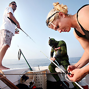 """Captain Lindsey Shuford watches as Kenneth Kelly and Kelsey Albert prepare their spearfishing gear, including guns, spears, tips and lines before freediving off the coast of North Carolina. """"Blood in the Water - Gear check"""""""