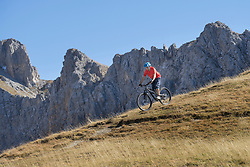 Mountain biker riding down hill in alpine landscape, Tyrol, Austria
