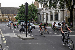 © London News Pictures. 25/08/2016. The majority of cyclists ignore the cycle lane on Parliament Square in Westminster, London. Cyclists repeatedly ignore new cycle lanes installed around westminster in central London. Between the hours of 8am and 9am on Wednesday 24/08/2016, 266 (two hundred and sixty six) cyclists passed through the red light at one of the newly installed bike lanes and only 15 (fifteen) cyclists stopped.  The light system is designed to allow either vehicles or cyclists to pass at one time in order to make the junction safer for cyclists..... **VIDEO AVAILABLE** Photo credit: London News Pictures.