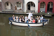 Een meisje vaart met haar vriendinnen op haar vrijgezellenfeest in een boot door de Oudegracht in Utrecht.<br />