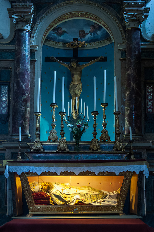 """A view of the altar and of the statue of S. Ildebrando of San Donato church in the village of Civita di Bagnoregio.<br /> Civita di Bagnoregio is a town in the Province of Viterbo in central Italy, a suburb of the comune of Bagnoregio, 1 kilometre (0.6 mi) east from it. It is about 120 kilometres (75 mi) north of Rome. Civita was founded by Etruscans more than 2,500 years ago. Bagnoregio continues as a small but prosperous town, while Civita became known in Italian as La città che muore (""""The Dying Town""""). Civita has only recently been experiencing a tourist revival. The population today varies from about 7 people in winter to more than 100 in summer.The town was placed on the World Monuments Fund's 2006 Watch List of the 100 Most Endangered Sites, because of threats it faces from erosion and unregulated tourism."""