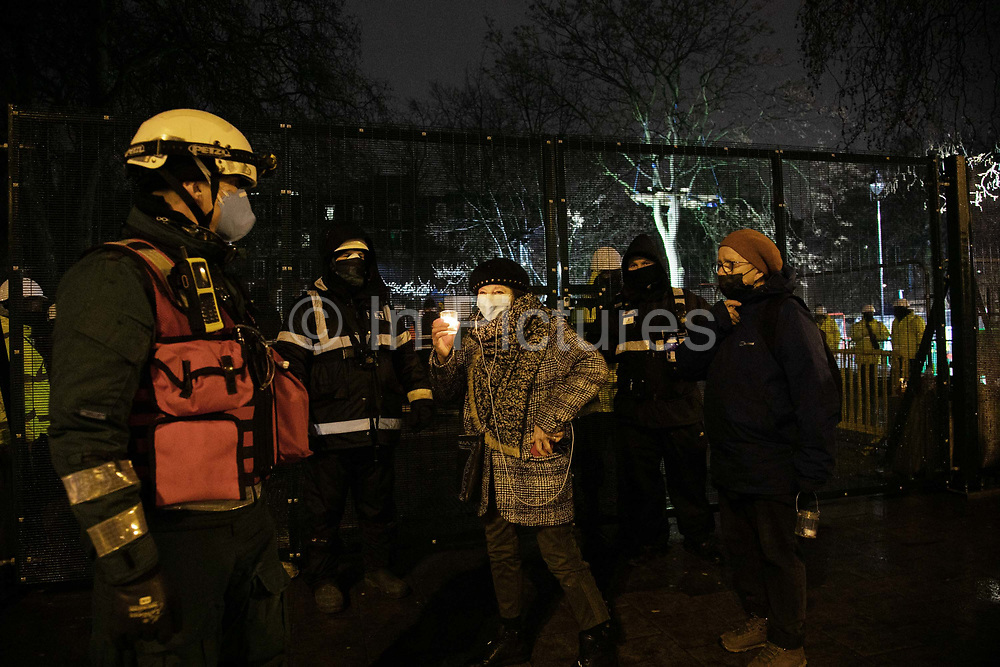 Environmental anti-HS2 activists attend a candlelit vigil at Euston Gardens on the 6th of February 2021, London, United Kingdom. Anti HS2 campaigners and climate activists have occupied the garden and the trees outside Euston train station for months. The vigil is for the trees which have already been cut down and to commemorate the climate activist Iggy Fox Raphaël Coleman who died a year ago. Because of Covid-19 restrictions all were asked to constantly move and not stay too close. A number of tree protectors have been under ground for 11 days in tunnels dug out over months and bailiffs and the National Eviction Team are working day and night to dig them out. The high speed train project, HS2, will run from London to Birmingham, Manchester and Leeds and it is estimated to cost around 100bn pounds. The garden and trees have to go because HS2 wants to build a temporary taxi rank as part of the bigger high speed train project.