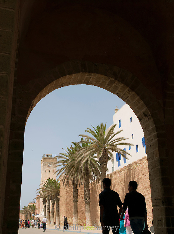 People walk through one of the entrance gates to the medina of Essaouira in Morocco