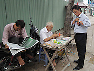 Man buying lottery tickets from elderly vendor next to a man on a motorbike reading the newspaper, HCMC, Vietnam, Southeast Asia