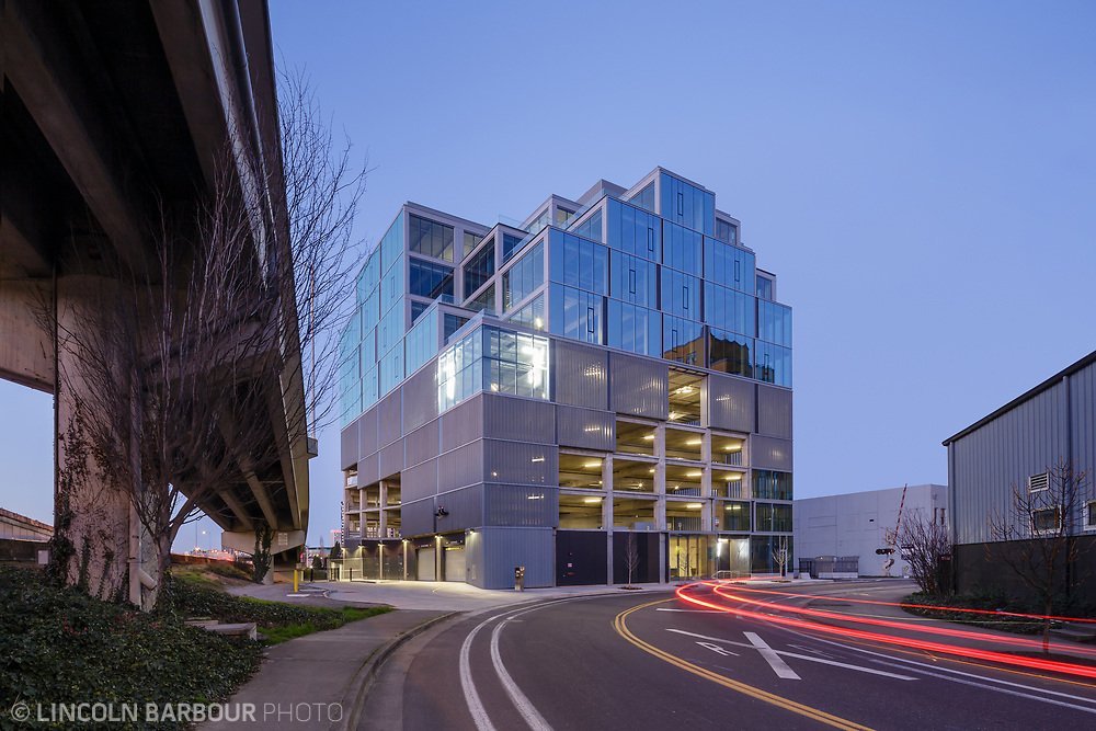 The 7 Stark Building at dusk next to an onramp for the neighboring highway in Portland, Oregon.  Car tail lights streak by in the foreground.