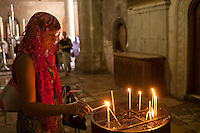 A shrouded woman lights a candle in a temple in Jerusalem.