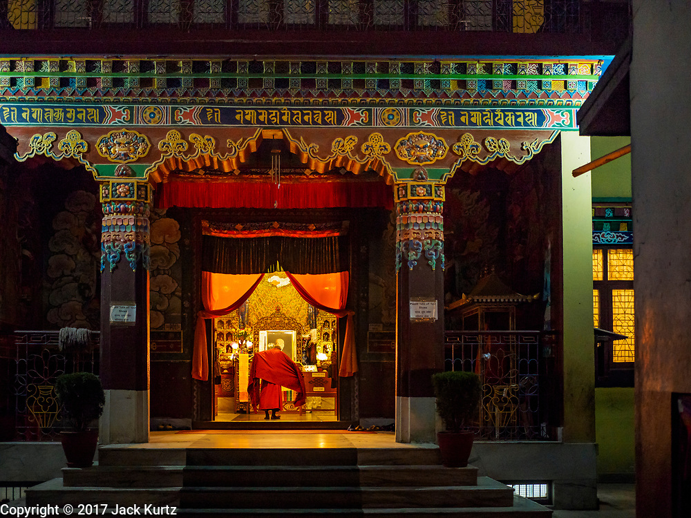 17 MARCH 2017 - KATHMANDU, NEPAL: A Buddhist monk adjusts his robes in the prayer hall of a monastery before morning prayers at Boudhanath Stupa in Kathmandu. There are several Tibetan monasteries around the stupa, which is the holiest site in Nepali Buddhism. It is also the center of the Tibetan exile community in Kathmandu. The Stupa was badly damaged in the 2015 earthquake but was one of the first buildings renovated.     PHOTO BY JACK KURTZ