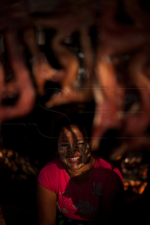 A women hides from the sun, with Thanaka powder on her face to protect her skin.<br /> Note: These images are not distributed or sold in Portugal